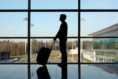 Hombre con el equipaje que coloca la ventana cercana en aeropuerto Imagen de archivo