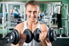 Hombre con el equipo de entrenamiento del peso foto de archivo libre de regalías