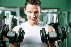 Hombre con el equipo de entrenamiento del peso imagen de archivo