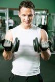 Hombre con el equipo de entrenamiento del peso imagenes de archivo
