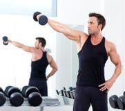 Hombre con el equipo de entrenamiento del peso en la gimnasia del deporte fotos de archivo