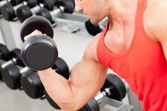 Hombre con el equipo de entrenamiento del peso en la gimnasia del deporte foto de archivo libre de regalías