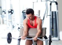 Hombre con el equipo de entrenamiento del peso en la gimnasia del deporte imagenes de archivo