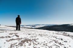 Hombre con el equipo del esquí en la tapa de las montañas Imágenes de archivo libres de regalías