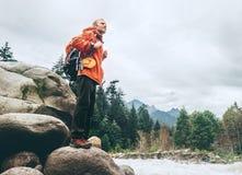 Hombre con el equipo turístico en la orilla del río de la montaña Imagenes de archivo