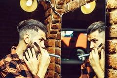 Hombre con el espejo cercano de la maquinilla de afeitar imagen de archivo