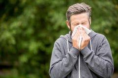 Hombre con el estornudo frío Imagenes de archivo