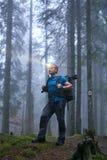 Hombre con el faro y la mochila en el bosque foto de archivo
