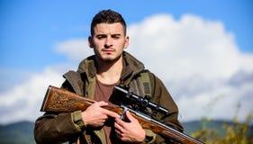 Hombre con el fondo de la naturaleza del equipo de la caza del rifle Asegúrese de la condición segura Prepárese para cazar Qué us imagen de archivo