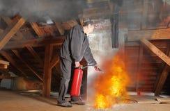 Hombre con el fuego de los agains del extintor que lucha en su casa foto de archivo