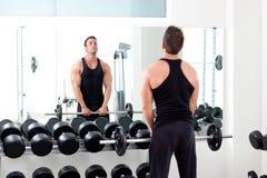 Hombre con el gimnasio del equipo de entrenamiento del peso de la pesa de gimnasia foto de archivo libre de regalías