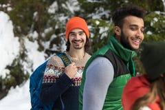 Hombre con el invierno de Forest Young Friends Walking Outdoor de la nieve del grupo de la gente de la mochila Imágenes de archivo libres de regalías