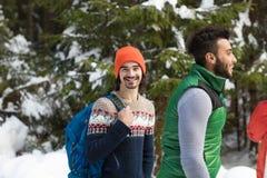 Hombre con el invierno de Forest Young Friends Walking Outdoor de la nieve del grupo de la gente de la mochila Fotografía de archivo libre de regalías