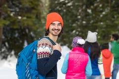 Hombre con el invierno de Forest Young Friends Walking Outdoor de la nieve del grupo de la gente de la mochila Fotos de archivo