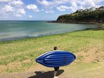 Hombre con el kajak en la playa de Cornualles Imagenes de archivo