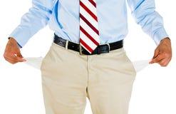 Hombre con el lazo, los pantalones de color caqui, la camisa de vestir, y la correa, sacando el bolsillo vacío Imagenes de archivo