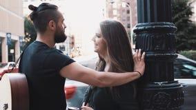 Hombre con el ligón de la guitarra y de la muchacha en la calle Charla caucásica romántica que sonríe en la calle, sonrisa de los almacen de metraje de vídeo