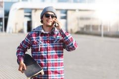 Hombre con el monopatín y el teléfono Fotografía de archivo