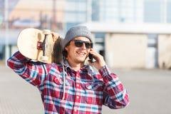Hombre con el monopatín y el teléfono Imagen de archivo
