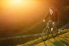 Hombre con el montar a caballo rojo de la mochila en la bicicleta de la montaña en un rastro con el sol brillante en la puesta de Foto de archivo