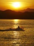 Hombre con el moto-barco en puesta del sol Imágenes de archivo libres de regalías