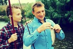 Hombre con el muchacho del adolescente que lanza pescados del gancho Imagen de archivo libre de regalías