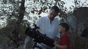 Hombre con el muchacho que usa el telescopio imagen de archivo libre de regalías