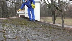 Hombre con el musgo limpio de la máscara protectora de la presión de agua del tejado 4K metrajes