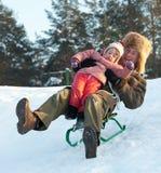 Hombre con el niño que resbala en downhil de los trineos Imagen de archivo libre de regalías