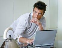 Hombre con el ordenador en cocina Imagenes de archivo