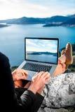 Hombre con el ordenador portátil en el top de la montaña Fotos de archivo
