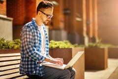 Hombre con el ordenador portátil en la calle fotos de archivo