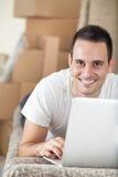 Hombre con el ordenador portátil en nuevo hogar Foto de archivo