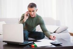 Hombre con el ordenador portátil que llama por teléfono y que toma a notas Foto de archivo libre de regalías