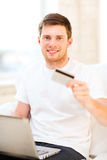 Hombre con el ordenador portátil que muestra la tarjeta de crédito en casa Imagen de archivo libre de regalías