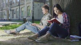 Hombre con el ordenador portátil que se sienta debajo de árbol y que mira el libro de lectura de la muchacha, afecto metrajes
