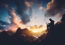 Hombre con el ordenador portátil que se sienta en las montañas foto de archivo