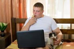 Hombre con el ordenador portátil y el gato divertido que comen el cono de helado en la cama Imagenes de archivo