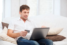 Hombre con el ordenador portátil y la tarjeta de crédito en casa Foto de archivo