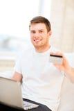 Hombre con el ordenador portátil y la tarjeta de crédito en casa Fotografía de archivo libre de regalías