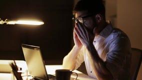 Hombre con el ordenador portátil y los papeles que trabajan en la oficina de la noche almacen de metraje de vídeo