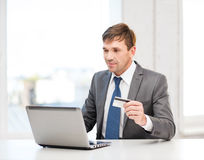 Hombre con el ordenador portátil y tarjeta de crédito en oficina imagen de archivo libre de regalías