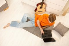 Hombre con el ordenador y la guitarra Imagen de archivo