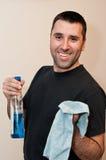Hombre con el paño que es feliz de limpiar la casa Imágenes de archivo libres de regalías