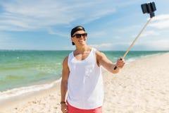 Hombre con el palillo del selfie del smartphone en la playa del verano Fotos de archivo