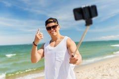Hombre con el palillo del selfie del smartphone en la playa del verano Imagenes de archivo