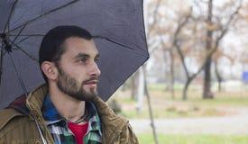 Hombre con el paraguas en el parque Imagen de archivo libre de regalías