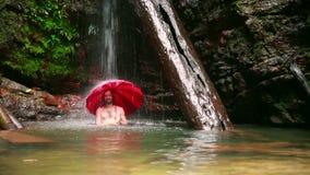 Hombre con el paraguas en la cascada en la selva tropical de Borneo metrajes