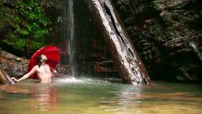 Hombre con el paraguas en la cascada en la selva tropical de Borneo almacen de metraje de vídeo