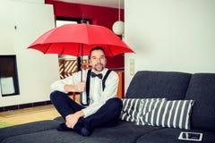 Hombre con el paraguas en la sala de estar foto de archivo
